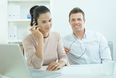 Couple working at home. Couple working on laptop computer at home office, happy, smiling. Woman calling on mobile phone Royalty Free Stock Photography