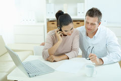 Couple working at home. Couple working on laptop computer at home office, happy, smiling. Woman calling on mobile phone Royalty Free Stock Photo