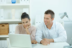 Couple working at home. Young casual couple sitting  at desk working together at home office, smiling, happy, using laptop computer Royalty Free Stock Image