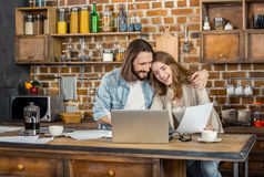 Couple working at home. Couple working with laptop while standing in kitchen Royalty Free Stock Photos