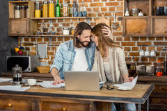 Couple working at home. Couple working with laptop while standing in kitchen Stock Photography