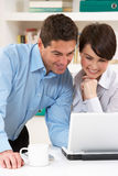 Couple Working From Home Using Laptop. Smiling Royalty Free Stock Photography
