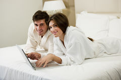 Couple Working iI Bed Stock Image