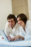 Couple Working iI Bed Stock Images