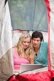 Couple working on laptop while camping. Young couple using laptop in tent while camping stock photography