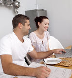 Couple working with a laptop in kitchen. Young couple working with a laptop in kitchen Stock Image