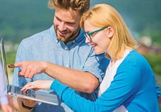 Couple working laptop outdoor sunny day, nature background. Man and girl interested information screen notebook. Mobile royalty free stock images