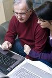 Couple working on laptops. Adult couple working on laptops stock image