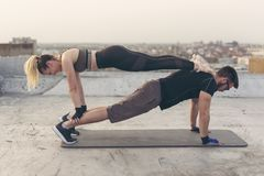 Couple doing a straight-arm plank exercise stock photography