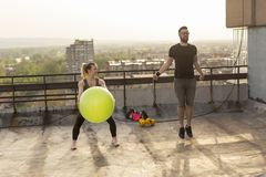 Couple working out. On a building rooftop terrace, jumping ropes and doing pilates ball exercises royalty free stock image