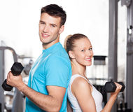 Couple working out with dumbbells. Young couple in health club Stock Image