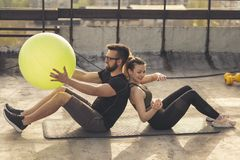 Couple working out with a pilates ball. Couple sitting back to back on a yoga mat on a building rooftop terrace, exercising by passing the pilates ball to each royalty free stock image