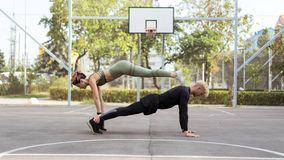 Couple working out on a sportsground, doing a straight-arm plank exercise stock photo