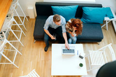 Couple working together in beautiful living room. With laptop on desk Royalty Free Stock Photography