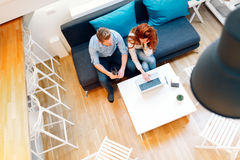 Couple working together in beautiful living room. With laptop on desk Royalty Free Stock Image