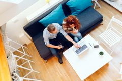Couple working together in beautiful living room. With laptop on desk Royalty Free Stock Photos