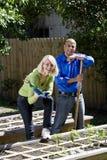 Couple working on vegetable garden in backyard Royalty Free Stock Photos