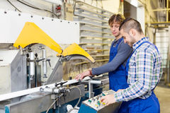 Couple of workmen at factory. A couple of happy adult men working around the milling machine at factory Stock Images