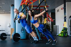 Sporty couple workout in the gym, doing exercise with functional loops. royalty free stock image