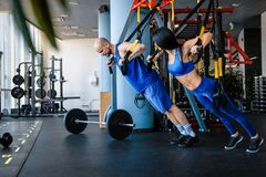 Sporty couple workout in the gym, doing exercise with functional loops. royalty free stock photos