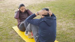 Couple workout outdoors. Latin american young couple do sit ups together on common yellow mat in autumn rainy park as a. Part of workout routine program stock video