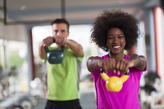 Couple  workout with weights at  crossfit gym. Healthy couple  workout with weights lifting  dumbbels at  crossfit gym african  american women with afro Stock Image