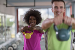 Couple  workout with weights at  crossfit gym. Healthy couple  workout with weights lifting  dumbbels at  crossfit gym african  american women with afro Stock Photo