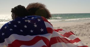 Couple wrapped in American flag sitting together on the beach 4k. Rear view of African american couple wrapped in American flag sitting together on the beach stock footage