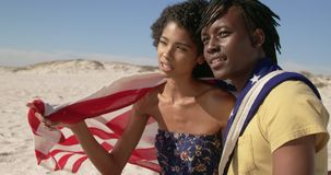 Couple wrapped in American flag sitting together on the beach 4k. Side view of African american couple wrapped in American flag sitting together on the beach stock video footage