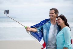 Couple wrapped in american flag taking selfie on beach. During winter Royalty Free Stock Photography