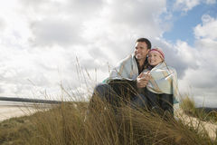Couple Wrapped In Blanket On Beach Royalty Free Stock Photos