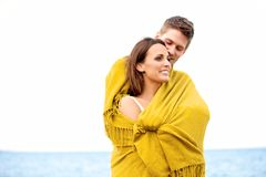Couple Wrapped with Blanket Embracing Stock Photo
