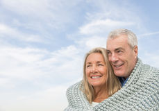 Couple Wrapped In Blanket Looking Away Against Sky. Happy senior couple wrapped in blanket looking away against cloudy sky Stock Photos