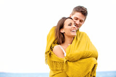 Couple Wrapped in Blanket Looking Happy Royalty Free Stock Images