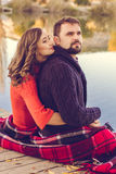 Couple are wrapped in a blanket near lake Royalty Free Stock Photo
