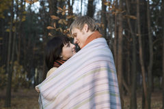 Couple Wrapped In Blanket Outdoors Stock Photo