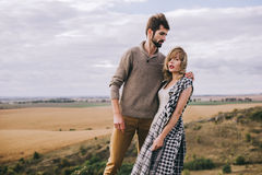 Couple wrapped in plaid standing on peak of mountain stock images