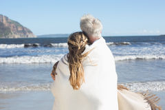 Couple wrapped up in blanket on the beach looking out to sea Stock Images