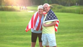 Couple wrapped in USA flag. Senior people smiling outdoors. Health of the nation. Value your roots stock video