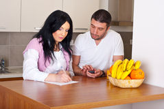 Couple writing and calculate their expenses Stock Images