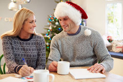 Couple Writing Christmas Cards Together Stock Image