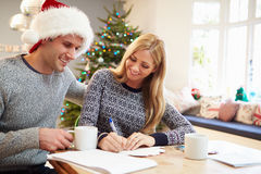 Couple Writing Christmas Cards Together Royalty Free Stock Image