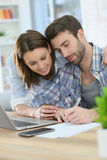 Couple writing notes and using laptop Royalty Free Stock Photo