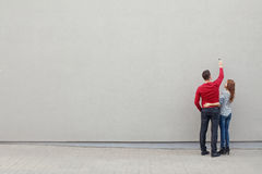Couple writing something on a blank wall Royalty Free Stock Image