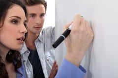 Couple writing on whiteboard Stock Photography