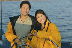 Couple In Yellow Anoraks At Steering Wheel Of Sailboat Royalty Free Stock Images