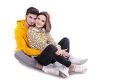 Couple in yellow hugging and sittin in white studio stock image