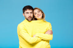 Couple in yellow sweater posing with crossed arms over blue background. Royalty Free Stock Photo