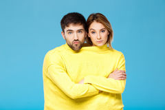 Couple in yellow sweater posing with crossed arms over blue background. Royalty Free Stock Images