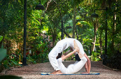 Couple yoga circle. Couple Yoga of men doing chakrasana and women doing dhanurasana poses in white cloth in the garden. Represents yin and yang stock image